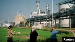 FILE - Workers walk past Jilin Fuel, one of the world's largest fuel ethanol plants, near the provincial capital Changchun of China's northeast Jilin province, early Sept. 2003.