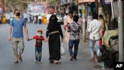 Keluarga Muslim India pulang ke rumah setelah berbelanja saat tiga jam jeda pembatasan jarak aman, di New Delhi, India, 25 April 2020.