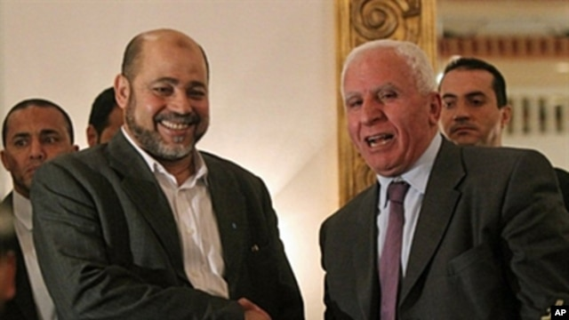 Palestinian Fatah delegation chief Azzam al-Ahmed (R) shakes hands with Hamas deputy leader Mussa Abu Marzuq after a joint press conference in Cairo, Egypt, April 27, 2011