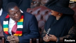 Zimbabwean President Emmerson Mnangagwa looks on next to his wife Auxillia Mnangagwa during the state funeral of the country's founder and longtime ruler Robert Mugabe