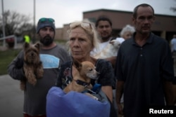FILE - Julie holds her dog Pee-wee as they stand in line to be evacuated to Austin after losing their home to Hurricane Harvey in Rockport, Texas, Aug. 26, 2017.