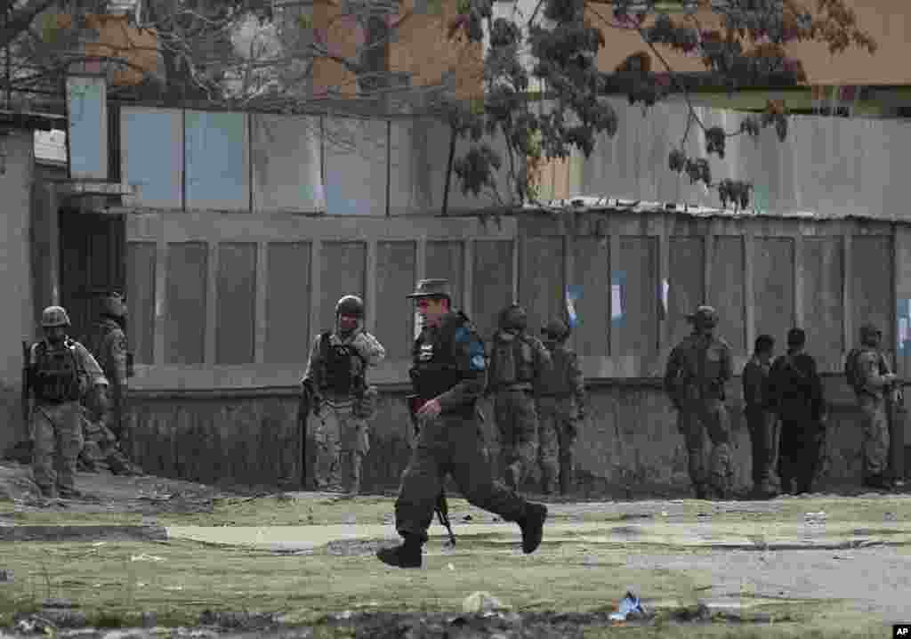Afghan police and special forces surround the area after suicide bombers armed with assault rifles and hand grenades attacked a guesthouse used by foreigners in Kabul, March 28, 2014.