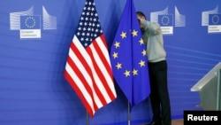 一名工作人員在歐盟與美國貿易談判的會場調整歐盟和美國的旗幟。(2013年11月11號)