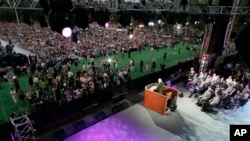Photographers and spectators approach the stage as Rev. Billy Graham preaches on the first night of his three-day crusade at Flushing Meadows Corona Park in the Queens borough of New York Friday, June 24, 2005. (AP Photo/Julie Jacobson)