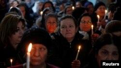 خواتین میں شمع روشن کیے چرچ میں داخل ہو رہی ہیں