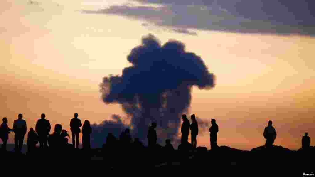 Turkish Kurds watch the smoke rises from Syrian town of Kobani near the Mursitpinar border crossing, on the Turkish-Syrian border in the southeastern town of Suruc, Sanliurfa province, Oct. 18, 2014.
