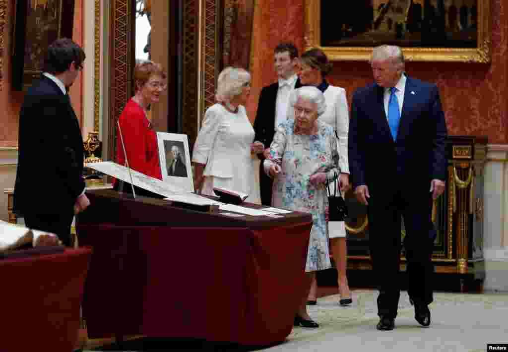 Президент США Дональд Трамп и королева Великобритании Елизавета Вторая рассматривают экспонаты королевской коллекции в Букингемском дворце. 3 июня 2019.
