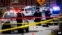 FILE - Crime scene investigators collect evidence from the pavement as police respond to an attack on campus at Ohio State University, in Columbus, Ohio, Nov. 28, 2016.