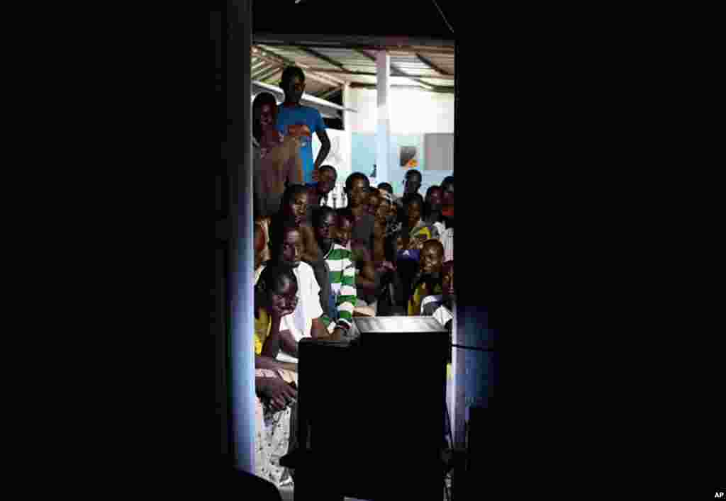 April 11: Local residents gather around a TV as they wait for the start of an address by leader Alassane Ouattara, hours after the capture of strongman Laurent Gbagbo, in the village of Kossihen, outside Abidjan, Ivory Coast. (AP Photo/Rebecca Blackwell)