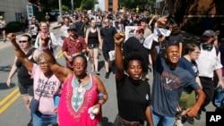 在维吉尼亚州夏洛茨维尔,反对种族主义的示威者沿着城市街道游行。
