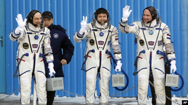 U.S. astronaut Donald Pettit (L), Russian cosmonaut Oleg Kononenko (C) and Dutch astronaut Andre Kuipers, members of the International Space Station (ISS) crew, wave before the launch of the Soyuz TMA-03M spacecraft at Baikonur cosmodrome, December 21, 20