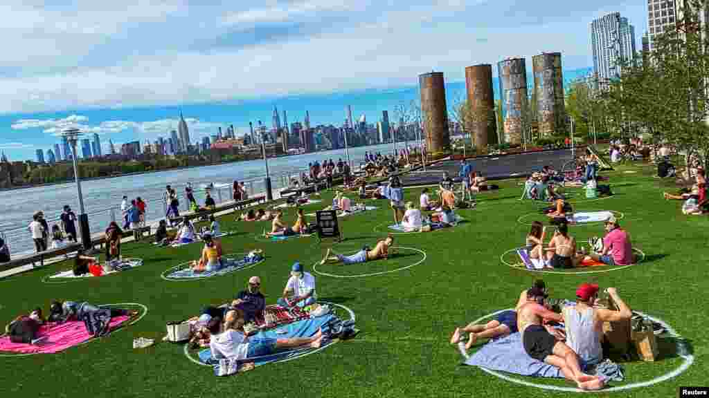 People try to keep social distance as they enjoy a warm day during the outbreak of the coronavirus disease (COVID-19) at Domino Park in Brooklyn, New York, May 16, 2020.