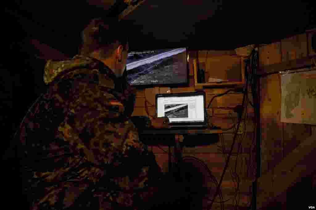 سرباز اوکراينی در سنگر زير زمينی خود از ابزار جاسوسی ويديويی برای نظارت بر جاده استراتژيک به فرودگاه دونتسک که در دست شورشيان قرار دارد استفاده می کند. زدوخورد در اطراف دونتسک همچنان ادامه دارد.عکس از آدام بيلز از صدای آمريکا.