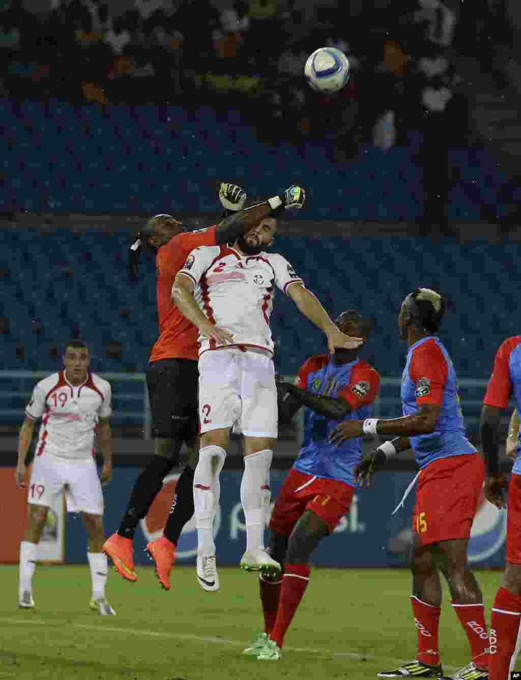Syam Youssef de la Tunisie, en haut à droite, est battu dans un duel aérien par le gardien de but de la RD Congo Robert Muteba Kidiaba, en haut à gauche, lors de leur match de la CAN Groupe B à Bata, en Guinée équatoriale, lundi 26 janvier 2015.