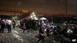 Petugas darurat memeriksa lokasi kecelakaan kereta Amtrak di Philadelphia (12/5). (AP/Joseph Kaczmarek)