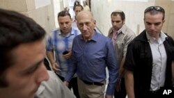 Former Israeli Prime Minister Ehud Olmert, center, arrives at Jerusalem's District Court for the hearing of the verdict in his trial July 10, 2012.