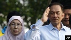 馬來西亞反對派領導人安華星期一(右)﹐站在妻子旁邊向民眾致意﹐之後他前往法院聽取有關他性犯罪的判決