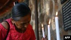 Una mujer enciende una vela en conmemoración de la masacre de El Mozote. Más de 75,000 personas fueron asesinadas o desaparecieron durante la guerra civil de El Salvador.