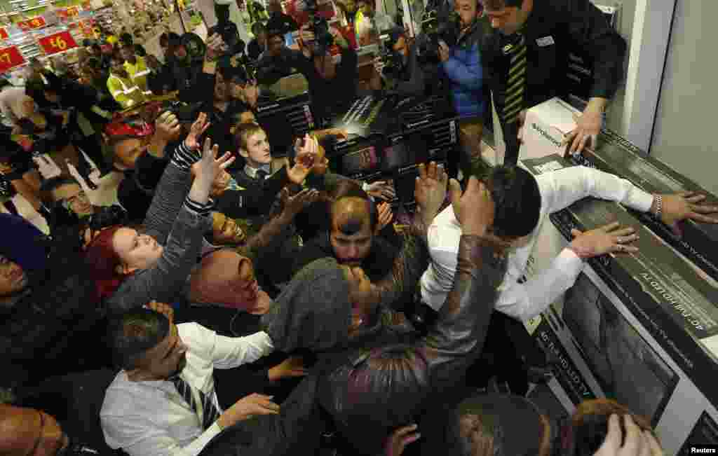 Orang-orang berebut barang di Black Friday di toserba Asda di Wembley, London utara, 28 November 2014.