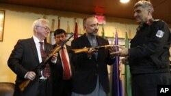 Rossiya elchisi Aleksandr Mantitskiy (chapda) AK-47 rusumidagi avtomatni Afg'oniston rasmiysi Muhammad Hanif Atmarga uzatmoqda. 24-fevral 2016-yil