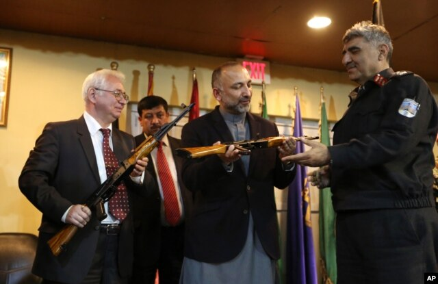 Russian Federation Ambassador Alexander Mantytskiy, left, hands over an AK-47 to Afghan National Security Adviser, Mohammad Hanif Atmar, center, at the International Kabul Airport, Feb. 24, 2016.
