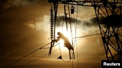 A technician works on an electricity pylon as part of maintenance of high-tension electricity power lines, during sunset in Roye, France, February 11, 2019.