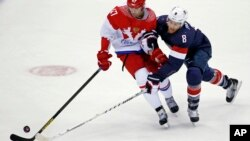 Russia forward Alexander Radulov and USA forward Joe Pavelski fight for the puck in the first period of a men's ice hockey game at the 2014 Winter Olympics, Feb. 15, 2014, in Sochi, Russia.