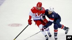 2014年2月15日在俄罗斯城市索契举行冬奥会的冰球比赛项目中,俄罗斯队员(左红衣)和美国队员(右蓝衣)激烈夺球的情况。