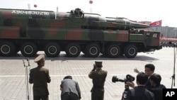 រថយន្តមួយគ្រឿងរបស់កូរ៉េខាងជើងដឹកនូវអ្វីដែលបង្ហាញថាជាកាំជ្រួចផ្លោងថ្មីឆ្លងកាត់ក្បួនព្យុហយាត្រាកងទ័ពងនៅ Kim Il Sung Square នៅរដ្ឋធានីព្យុងយ៉ាង ដើម្បីអបអរខួបទី១០០ឆ្នាំ ដោយចាប់តាំងពីការចាប់បដិសន្ធិរបស់ស្ថាបនិកកូរ៉េខាងជើងគឺលោក គីម