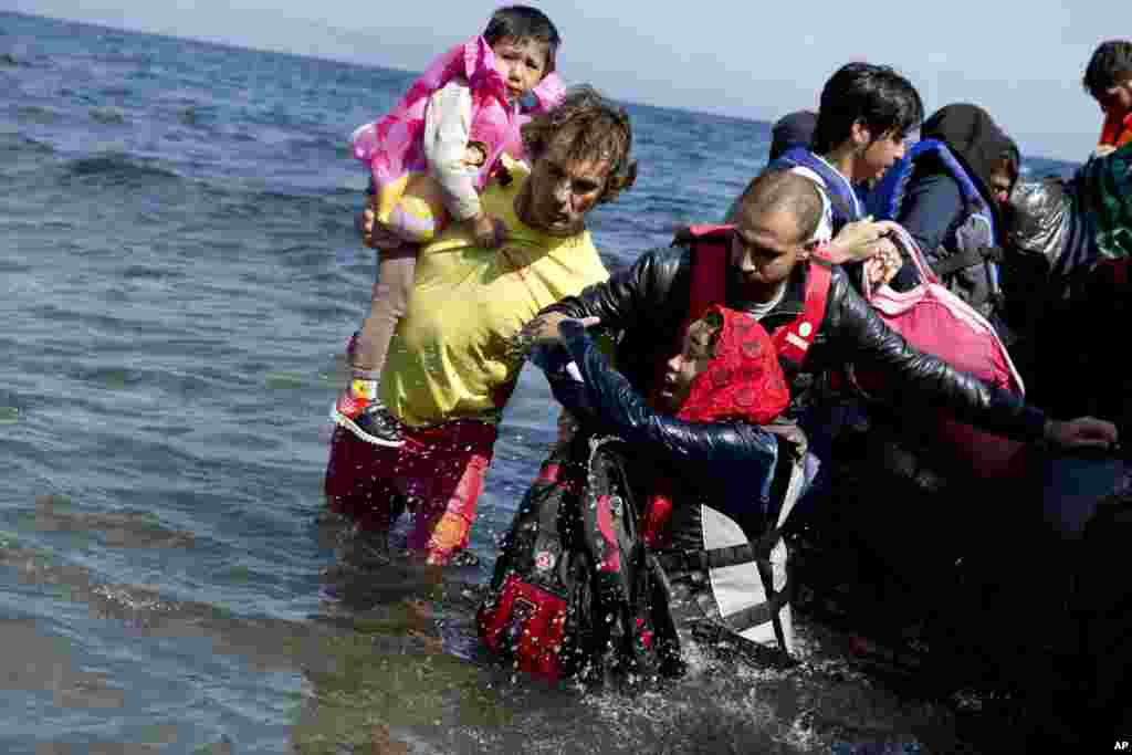 Afghan migrants arrive on the shores of the Greek island of Lesbos after crossing the Aegean sea from Turkey on a inflatable dinghy.
