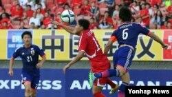 2일 중국 우한에서 열린 2015 동아시아축구연맹 축구선수권 대회 1차전에서 북한 선수와 일본 선수가 공을 다투고 있다.