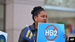 FILE - Cassandra Thomas of Human Rights Campaign holds a sign advocating the repeal of HB2 Dec. 7, 2016, in Charlotte, NC.