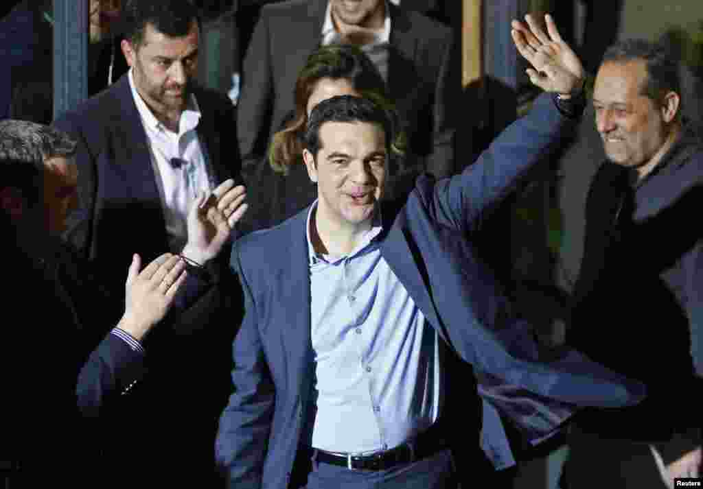 Head of radical leftist Syriza party Alexis Tsipras waves while leaving the party headquarters after his election victory, in Athens, Jan. 25, 2015.