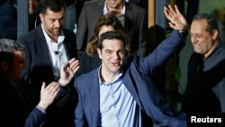 Head of Syriza party Alexis Tsipras waves while leaving the party headquarters after winning the elections in Athens, January 25, 2015.