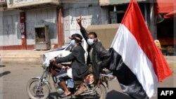 Những người biểu tình chống chính phủ ở Yemen cầm cờ quốc gia và di chuyển trên xe gắn máy trong cuộc biểu tình ở thủ đô Sanaa, Yemen hôm 22/11/11