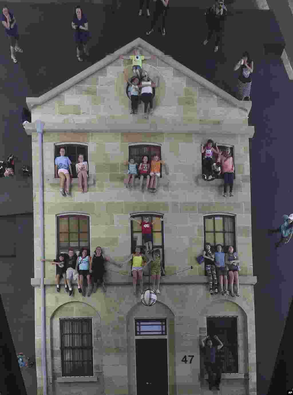 Para pengunjung pura-pura dalam posisi 'bergantung' di jendela sebuah gedung dalam pameran arsitektur unik di Sydney, Australia.