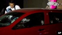 Un investigador toma fotos de uno de los autos en el que viajaban delincuentes que fueron abatidos a tiros por la policía en el estado mexicano de Sinaloa.