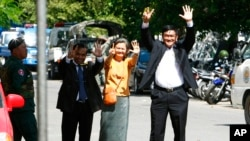 Cambodian lawmakers from the main opposition party of Cambodia National Rescue Party (CNRP), from right, Men Sothavrin, Mu Sochua and Keo Phirum gesture to make the number seven, the party's ballot number, as they are detained by authorities at Freedom Pa