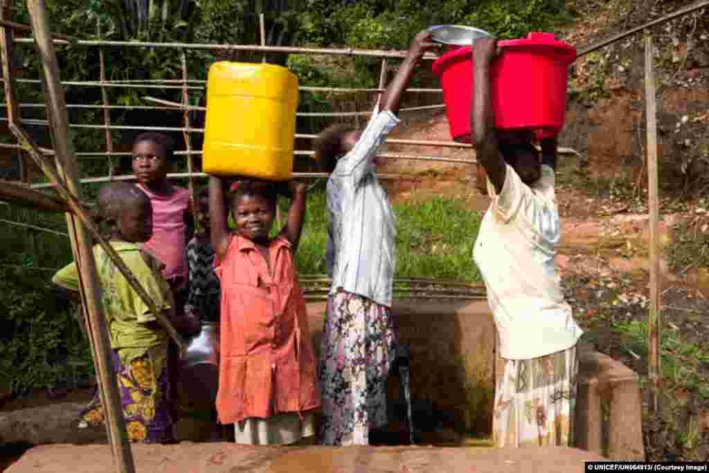 Mulheres e crianças vão abastecer-se de água num poço gerido pelo UNICEF emTshinyama, mna província congolesa do Kasai Oriental.