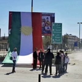 People stand in front of a Kurdish flag during a protest against Syria's President Bashar al-Assad and a celebration of Nowruz held by Qamishli's Kurdish community, March 21, 2012.