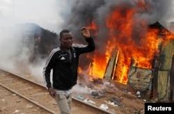 A supporter of opposition leader Raila Odinga runs past a burned shack, in Kibera slum, Nairobi, Kenya, Aug. 12, 2017.