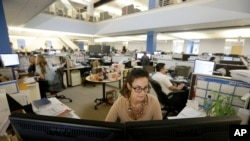 FILE - Tara Ostermann works at her desk at the Walmart.com office in San Bruno, California.