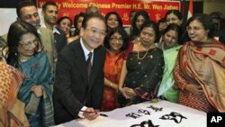 Chinese Premier Wen Jiabao writes an India-China friendship message during a visit to a school in New Delhi, India, 15 Dec. 2010.