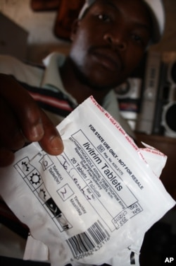 An HIV-infected patient holds a packet of antibiotics at a clinic in Mangaung
