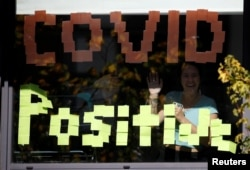 People wave through the window of a student accommodation building with a 'Covid Positive' sign displayed in it, following the outbreak of the coronavirus disease (COVID-19) in Manchester, Britain, September 27, 2020.