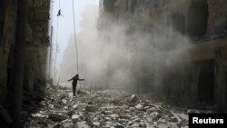 បុរសម្នាក់ដើរកាត់កម្ទេចអគារបន្ទាប់ពីមានការវាយប្រហារតាមអាកាសទៅលើតំបន់ដែលកាប់កាប់ដោយពួកឧទ្ទាមនៅជិតក្រុង Aleppo កាលពីថ្ងៃទី២៥ ខែកញ្ញា ឆ្នាំ២០១៥។