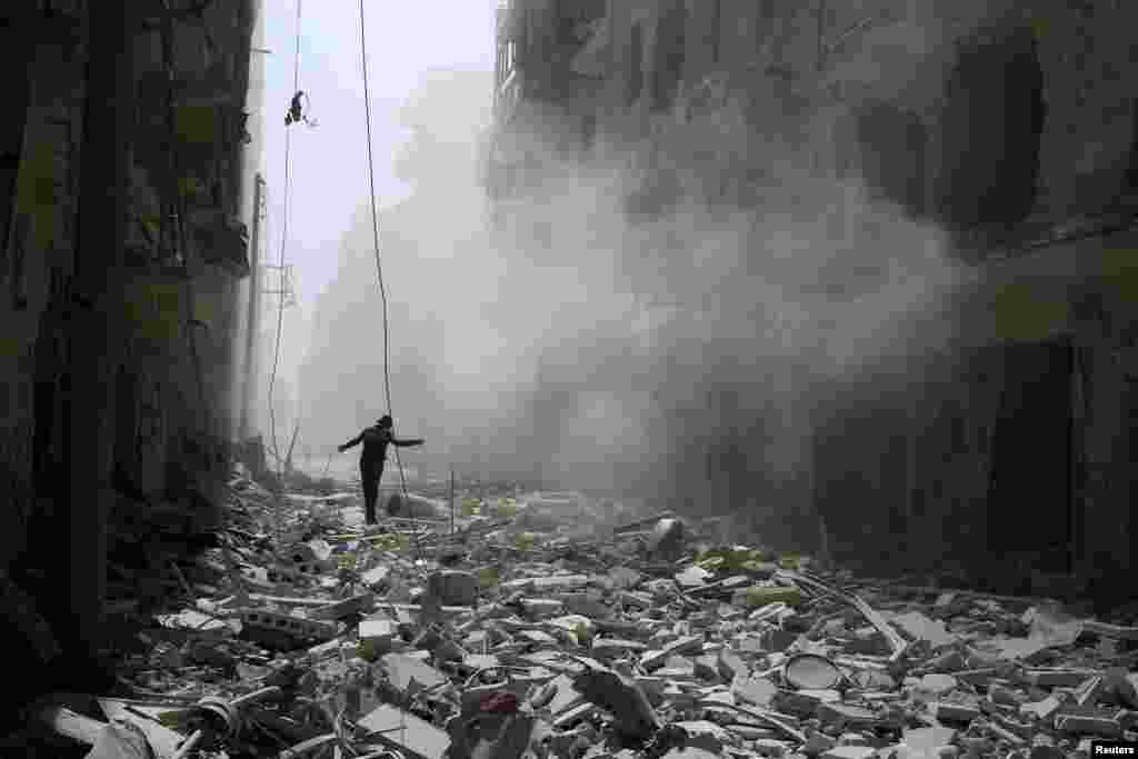 A man walks on the rubble of damaged buildings after an airstrike on the rebel held al-Qaterji neighbourhood of Aleppo, Syria, Sept. 25, 2016.