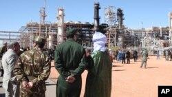 En esta foto del 31 de enero, de 2013, solados argelinos y autoridades frente a una planta de gas en Ain Amenas, vista al fondo, durante una visita organizada por autoridades argelinas para la prensa. EE.UU. dice que lanzó un ataque aéreo el 13 de junio, de 2015, contra el líder de al-Qaeda Mokhtar Bel Mokhtar, al quien responsabiliza por toma de la instalación.