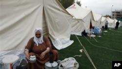 一名地震倖存者在凡省艾利克斯鎮足球場搭建的帳篷城內刷洗鍋碗