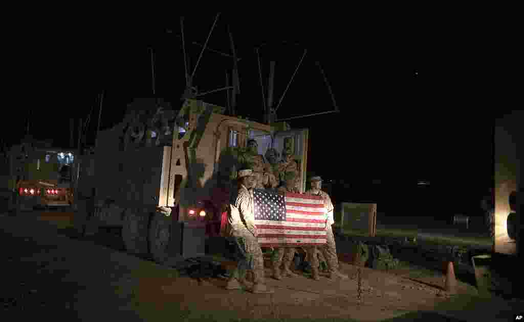 Soldiers with the 3rd Brigade Combat Team, 1st Cavalry Division pose with a US flag outside their Mine Resistant Ambush Protected (MRAP) vehicle before leaving Camp Adder to travel with the last US military convoy to leave Iraq, December 18, 2011. (Reuter